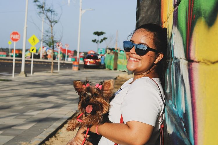 Smiling young woman with dog leaning on wall