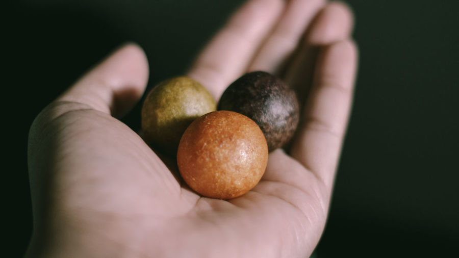 Close-up of hand holding apple against black background