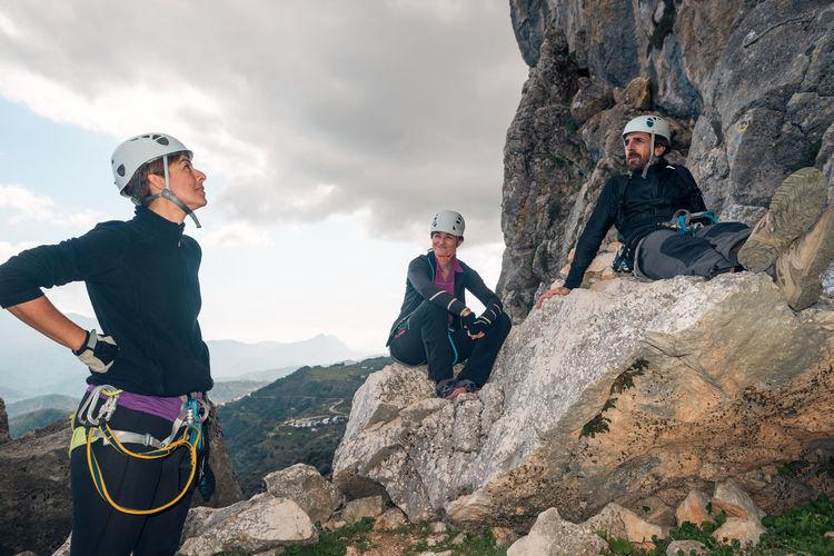 People on rock against mountain range