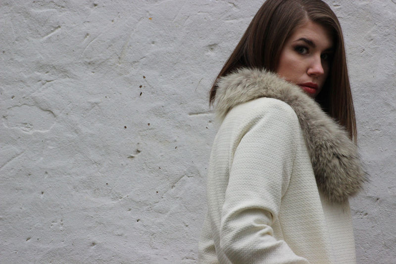 Side view of woman wearing fake fur standing by wall
