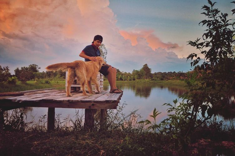 Man with dog standing in lake against sky