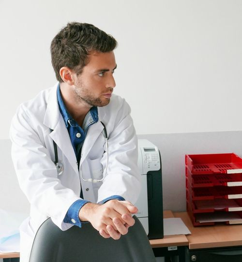 High Angle View Of Doctor Leaning On Chair In Office