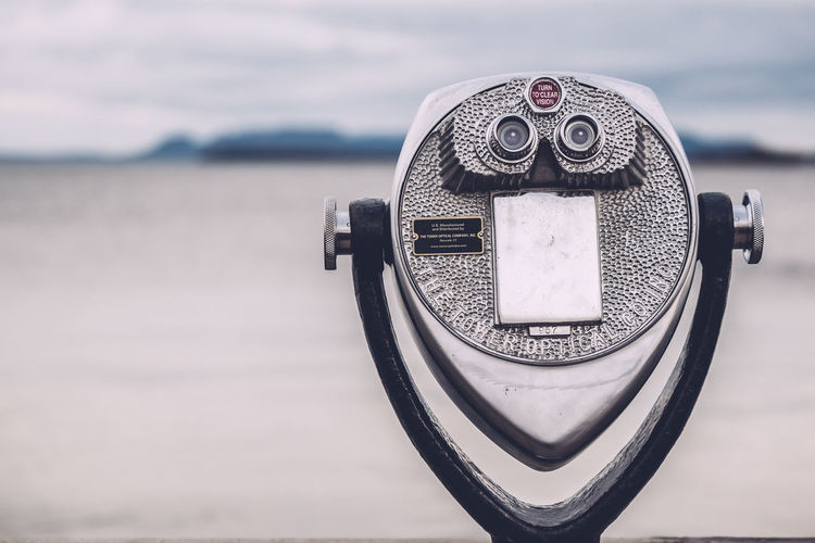 Close-up of coin-operated binoculars at beach against cloudy sky