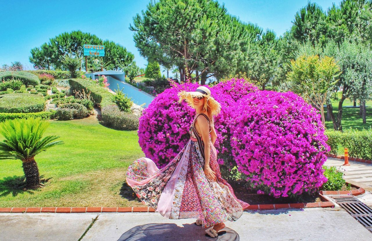 plant, real people, women, one person, leisure activity, lifestyles, tree, full length, nature, sky, day, adult, rear view, three quarter length, clothing, growth, flower, pink color, green color, fashion, outdoors, hairstyle