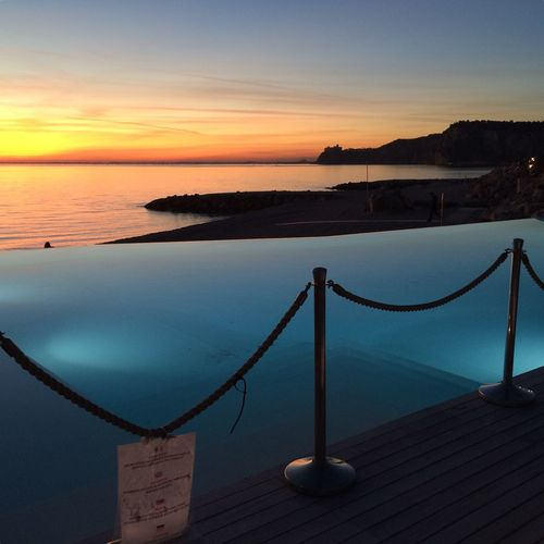 Infinity pool by sea against sky during sunset