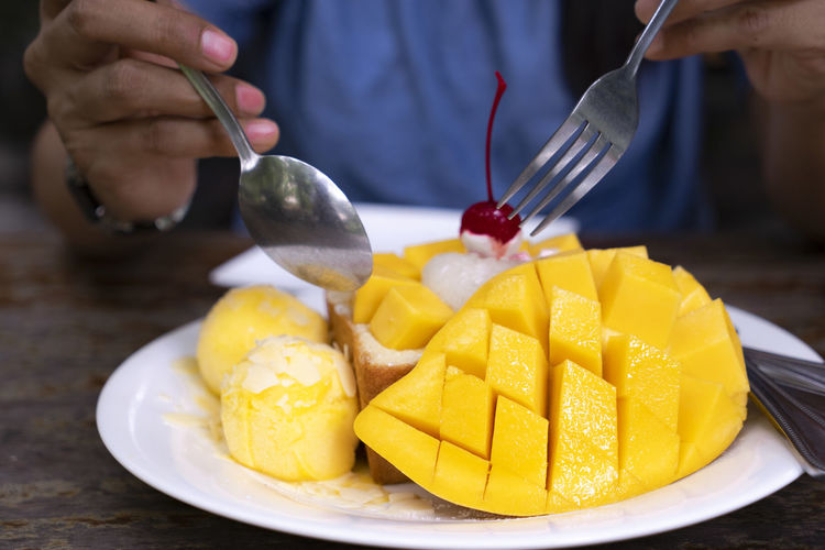 mango lover menu with fresh mango and mango ice cream Golden Mango Sweet Mango Mango Lover Mango Ice Cream Mango And Sticky Rice Sweet Food Indoors  Fork Human Hand Midsection Kitchen Utensil Real People One Person Freshness Food Food And Drink Eating Utensil Fruit Plate Table Hand Holding Spoon And Fork Start Eating Them
