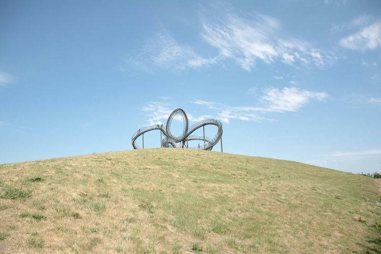 Low Angle View Of Rollercoaster On Hill Against Blue Sky