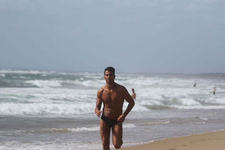 Shirtless young man running at beach against clear sky