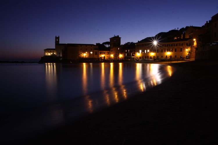 Illuminated historic building reflecting in sea against sky