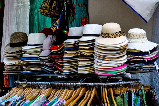 Hats and other clothing for sale in shop, Cascais, Portugal. Coat Hangers Choice Clothes Clothing Day Fashion Hanging Hat Hats Headwear Indoors  Large Group Of Objects Multi Colored No People Outdoors Retail  Shop Stack Store Sun Hat Variation