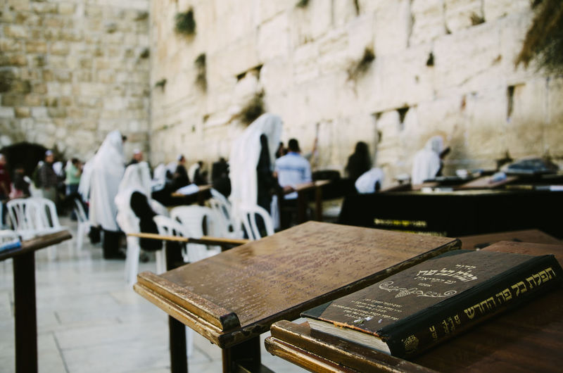 Torah on table with people standing by wailing wall