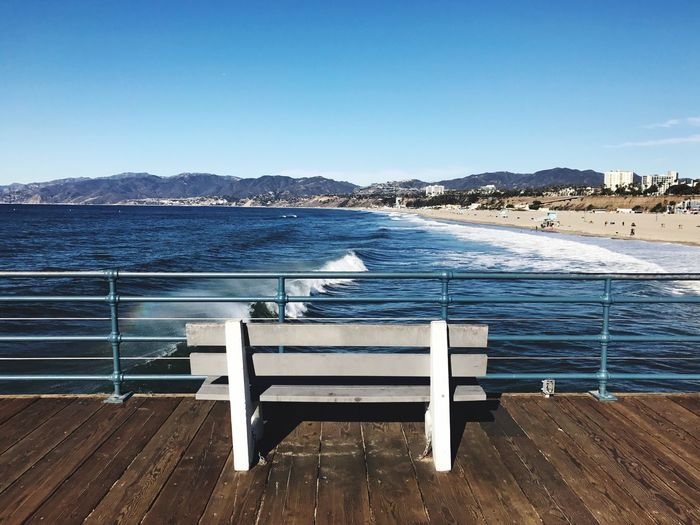 Empty Bench On Pier By Sea Against Clear Blue Sky