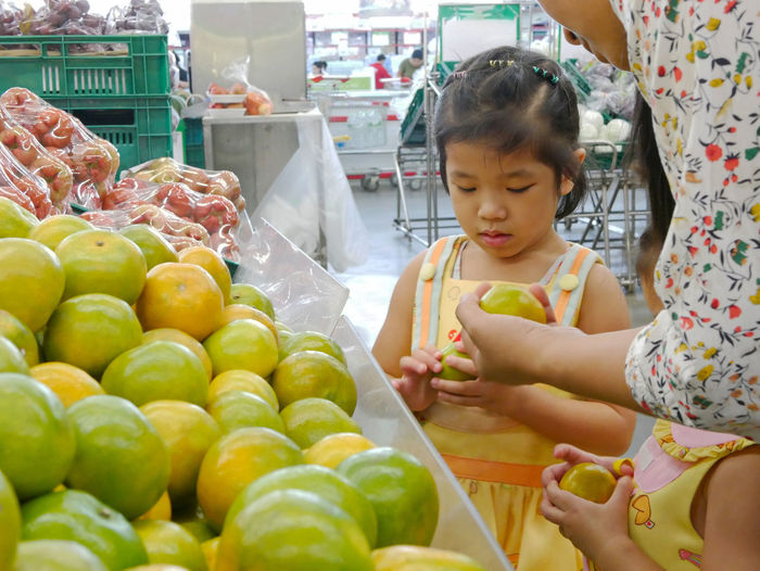 Midsection of mother giving oranges to daughters at market