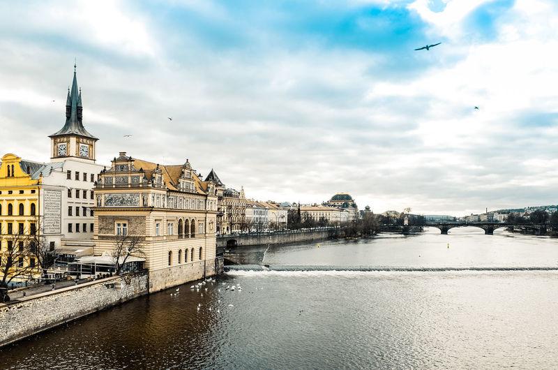 Buildings by vltava river against cloudy sky