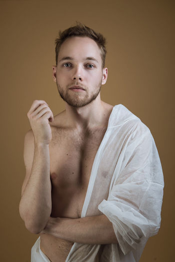 Portrait of confident young male model standing against brown background