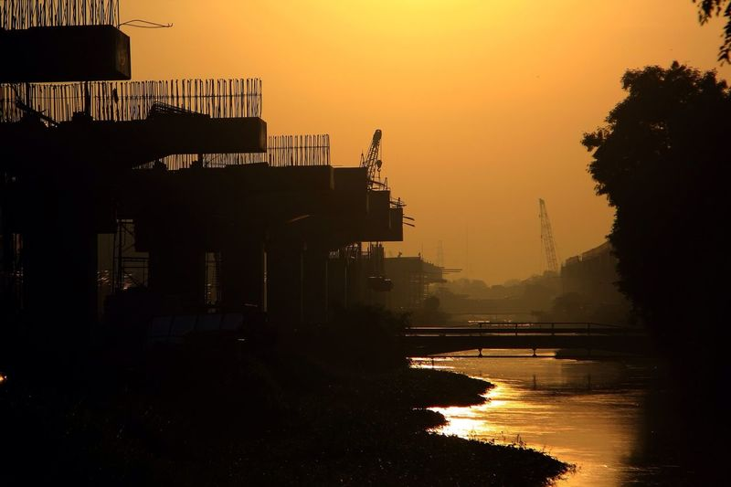 Silhouette Incomplete Bridge In River During Sunset