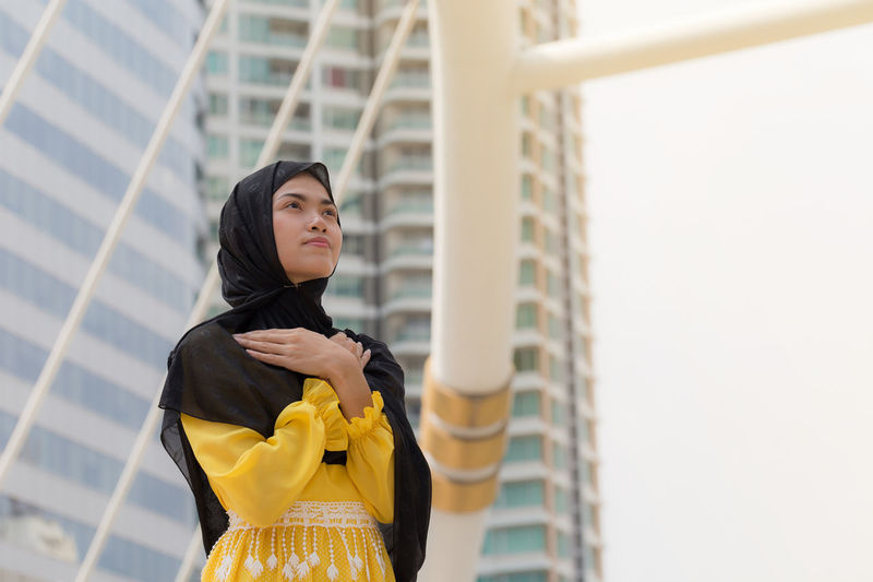 Low angle view of young woman wearing hijab while looking away in city