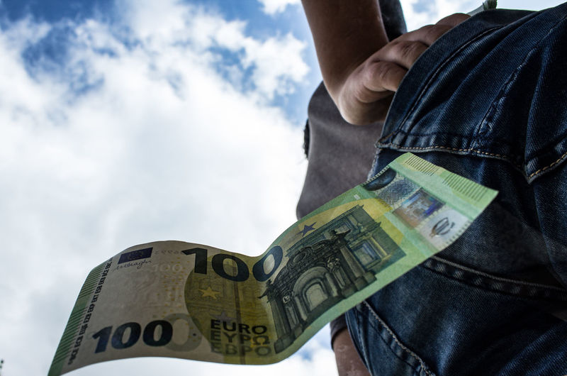 Low angle view of euro note falling from back pocket by man