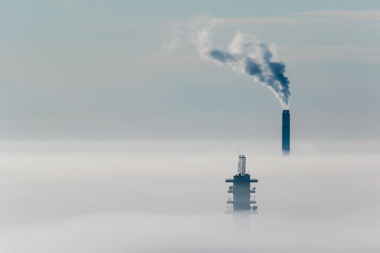 Smoke emitting from chimney against sky on a cold and foggy winter day