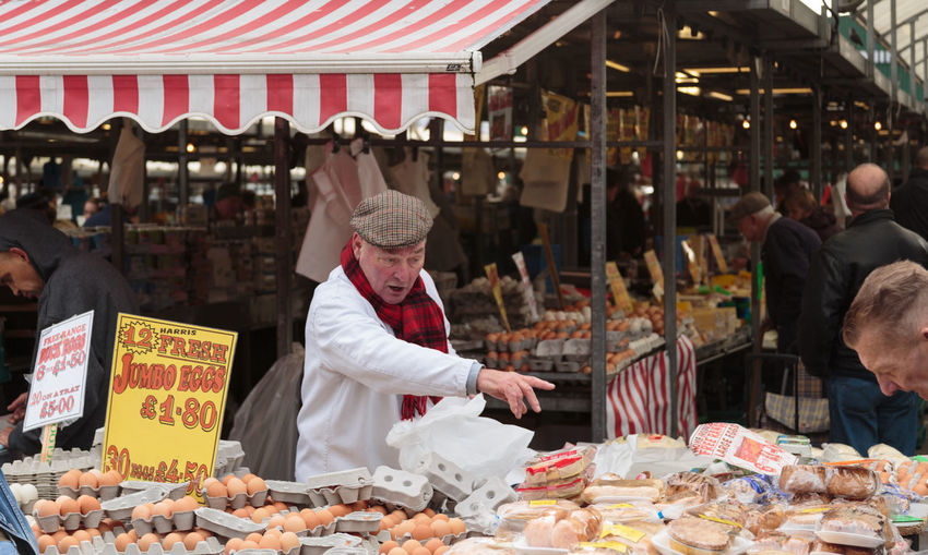 Butcher behind the counter on a stall at the open air market in Birmingham city centre. Abundance Choice Eggs Farm Produce Flat Cap Food Stall Food Stand For Sale Market Market Stall Older Person Pasties Pointing Red And White Stripes Retail  Retail  Sale Sandwiches Small Business Store