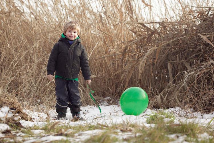 Full length portrait of happy boy standing in grass
