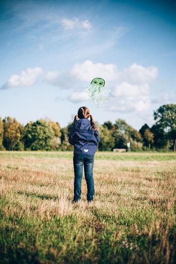 Rear view of girl flying kite on land against sky