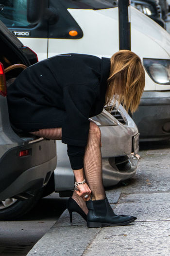 Side view of woman adjusting footwear while sitting in car trunk