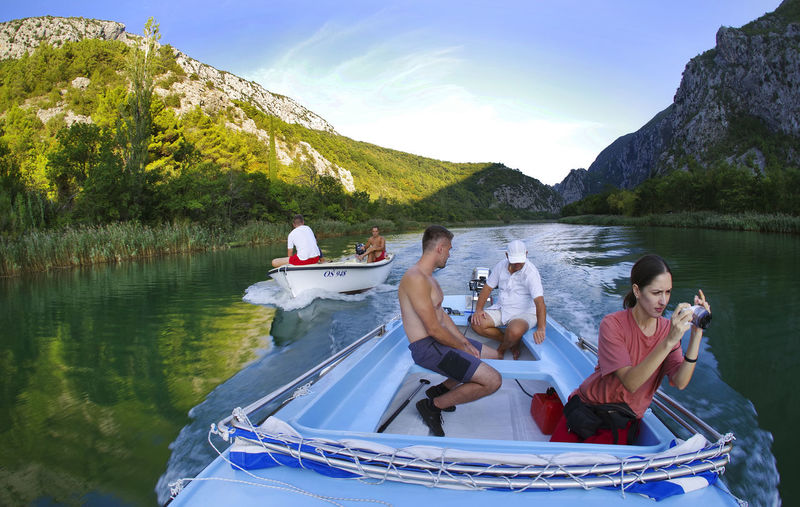 People sitting on boat in lake against mountains