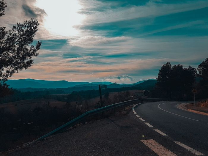 Tree Mountain Road Sunset Sky Landscape Mountain Range vanishing point Double Yellow Line Road Marking Country Road Winding Road Highway Dividing Line Car Point Of View Crash Barrier Diminishing Perspective Zebra Crossing Multiple Lane Highway Yellow Line Asphalt