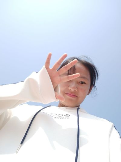 Low Angle Portrait Of Teenage Girl Gesturing Against Clear Sky