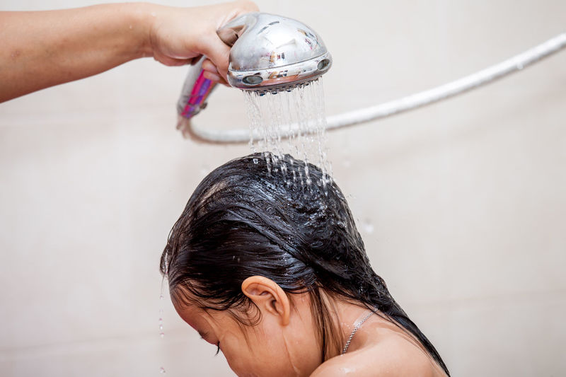 Cropped Hand Of Person Showering Girl In Bathroom