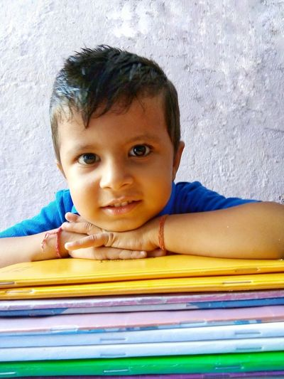 portrait of little boy with books Kid Indian Culture  Looking At Camera Smiling Confident  Education Knowledge Happiness Holiday Work Books Boy Asian  India Indoors  Window Light Cute Indian Child Childhood Facial Expression Portrait Elementary School School Children Schoolboy School Supplies Knowledge Back To School Elementary Student Homework