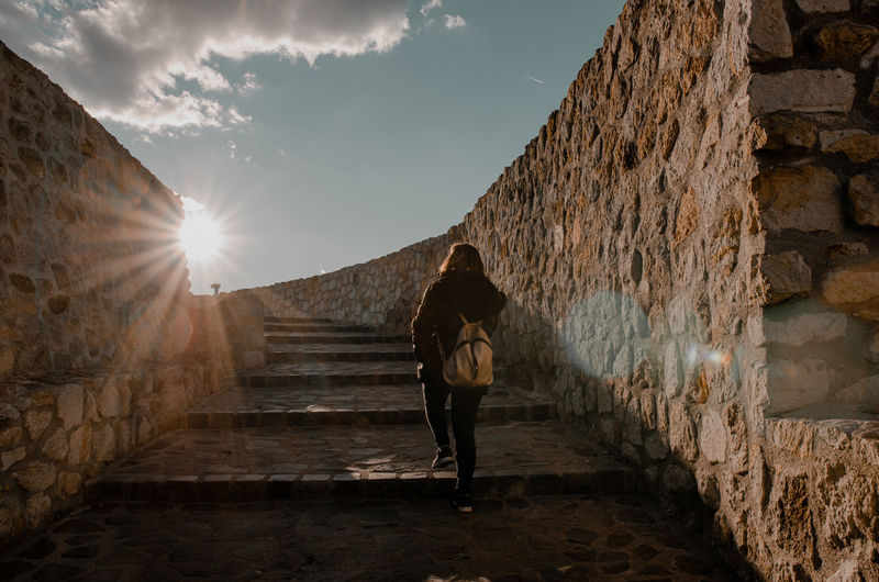 Rear view of woman walking on staircase against wall