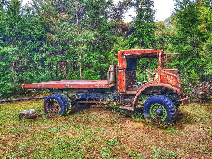 Abandoned tractor on field against trees