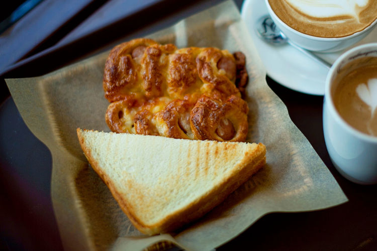 High angle view of sandwich with croissant and cappuccino served on table
