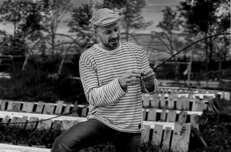 Smiling man preparing fishing bait while standing at park