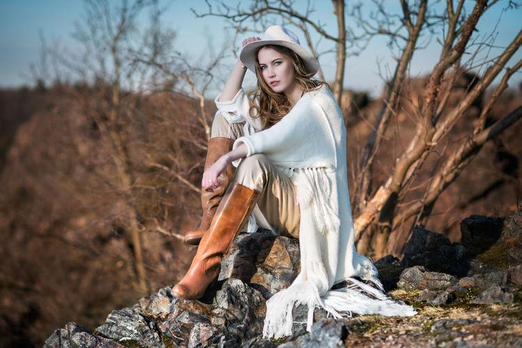 Portrait of fashionable woman sitting on rock