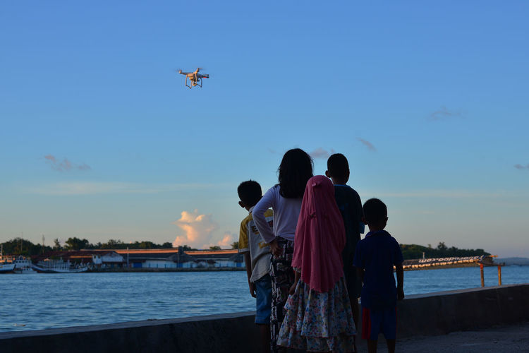 A group of childern feeling excited looking at flying drone at the port Kids Adult Beach Boys Child Childern Childhood Group Of People Leisure Activity Lifestyles Men Mode Of Transportation Nature Outdoors Real People Rear View Sea Sky Togetherness Transportation Water Women