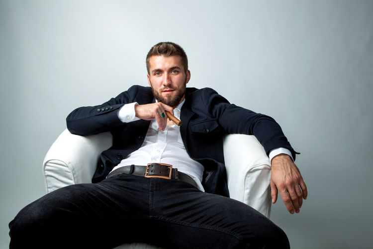 Portrait of a bearded businessman with a cigar, who is sitting in a white armchair and relaxing Males  Men Businessman Suit Cigar Smoke Handsome Beard Sitting Studio Shot Gray Background Relaxing Mafia  Armchair White Black Young Adult Casual Clothing Looking At Camera Career Thinking Confidence  Lifestyles Isolated Fashion