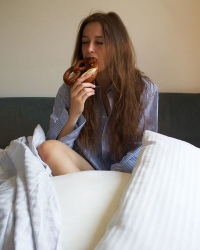 Young woman eating while sitting on bed at home