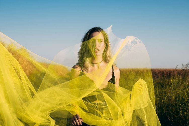Portrait of woman holding netting while standing against plants