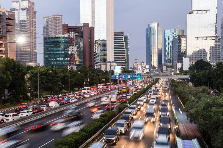 Traffic on road amidst buildings in city