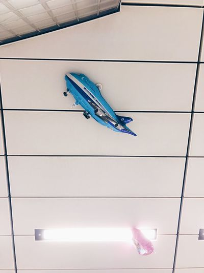 Low angle view of airplane flying against wall