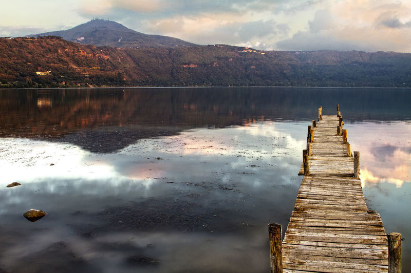 Pier By Lake Against Mountains