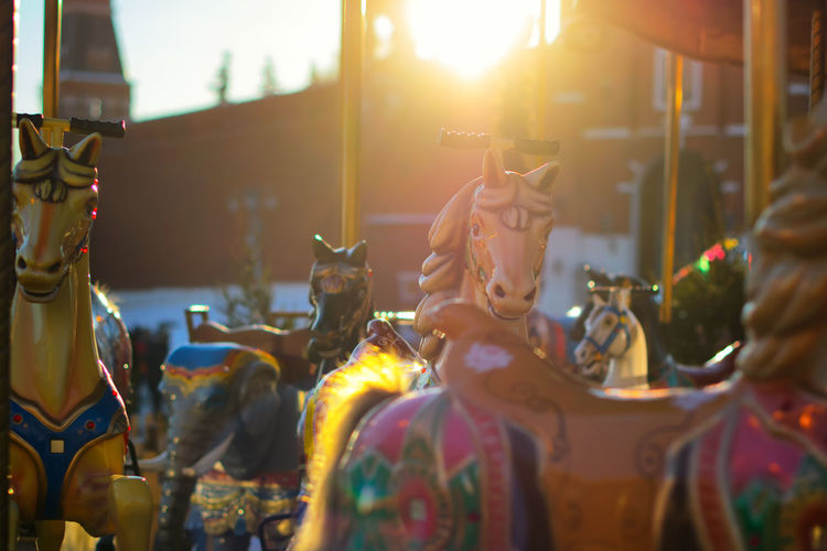 Close-up of carousel horses at amusement park during sunset