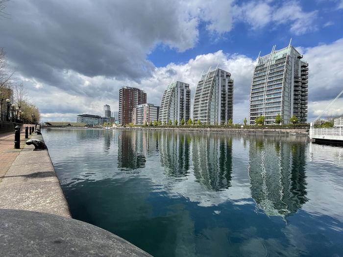 Swimming pool by lake against buildings in city