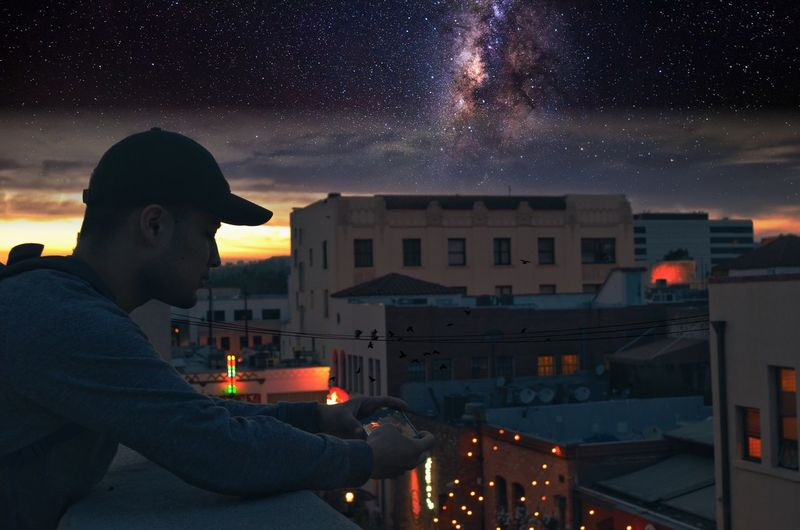 view of man using smart phone on balcony at night