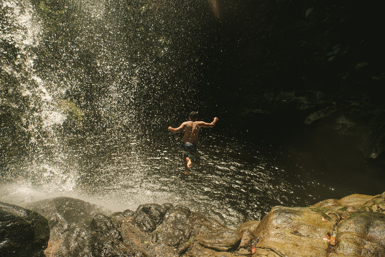 High angle view of shirtless man diving into water