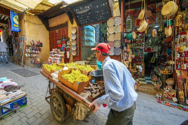 Guy pushing fruits, just another day. Fes Morocco Medina Medina De Fez Fes Morocco Ancient Real People Men Retail  Food Food And Drink Market Small Business Business Adult One Person Occupation Choice Market Stall Freshness Three Quarter Length Large Group Of Objects For Sale Casual Clothing Selling Store Vendor Sale Retail Display Buying Outdoors