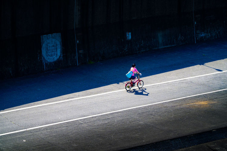 High angle view of woman riding bicycle on road